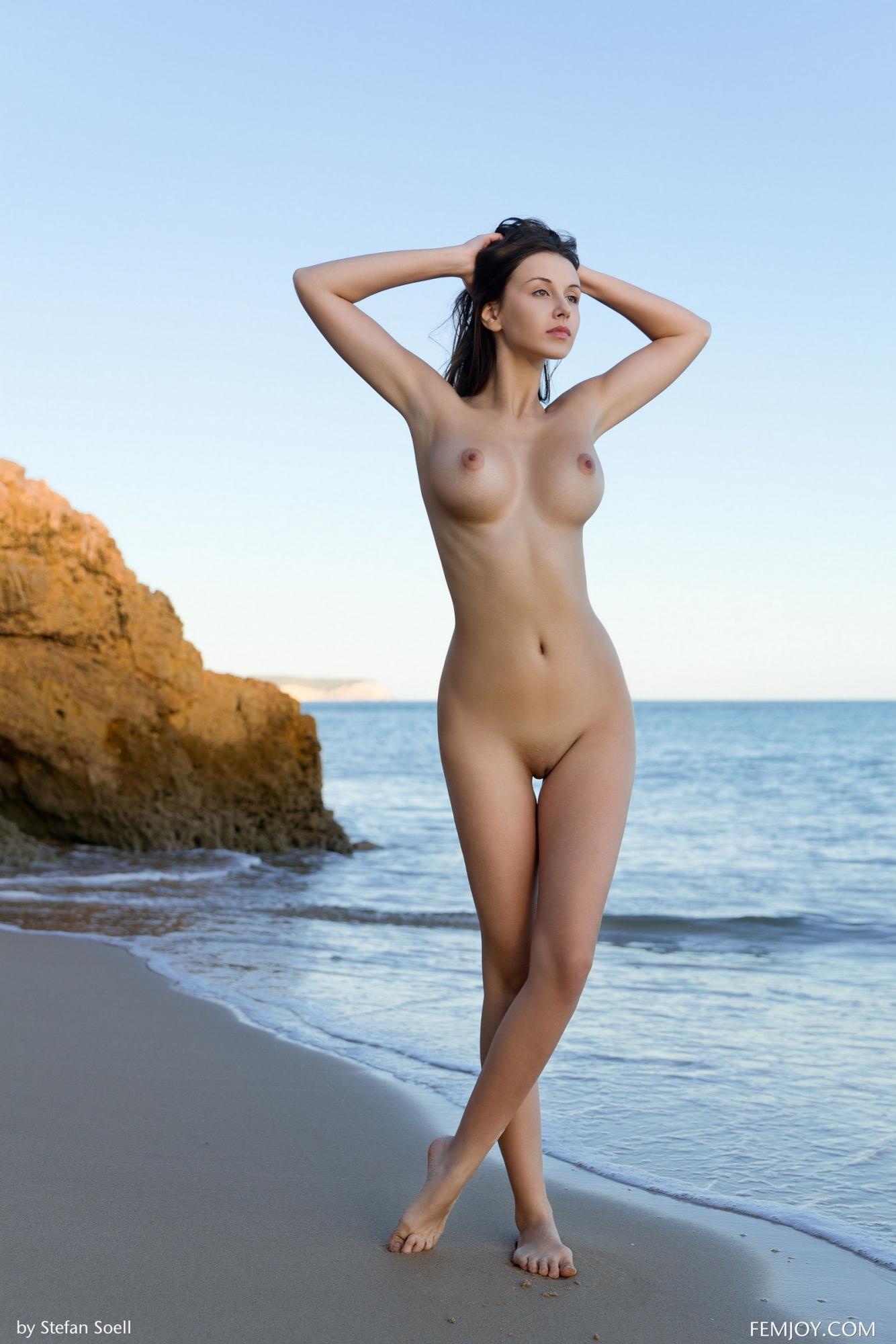 Красивая оголенная девушка позирует на пляже